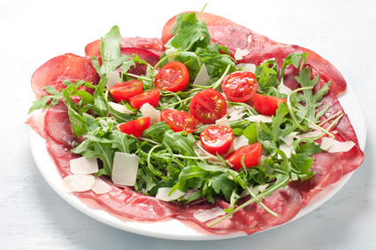 Plate of bresaola with rocket parmesan and cherry tomatoes